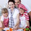 Family cutting colourful vegetables in kitchen — Stock Photo #10298654