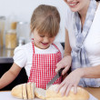 Mother and daughter cutting bread — Stock Photo