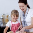 Mother teaching daughter how to cut bread — Stock Photo