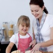 Mother teaching daughter how to cut bread - Stock Photo
