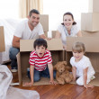 Family moving house with boxes around — Stockfoto