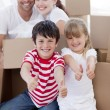 Family moving house with boxes and thumbs up - ストック写真