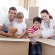 Family moving home with boxes around — Stock Photo