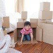 Kid playing with boxes in new house — Stock Photo