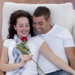 Portrait of lovers on sofa with a rose — Stock Photo