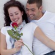 Couple on sofa with a rose — Stock Photo