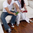 Couple on sofa playing video games - Stock Photo