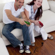 Couple playing video games in living-room — Stockfoto