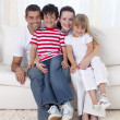 Family sitting on sofa together — Stock Photo #10298746