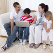 Smiling family in living-room using a laptop — Stock Photo