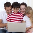 Royalty-Free Stock Photo: Family at home playing with a laptop