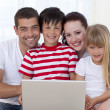 Portrait of family at home using a laptop - Stock Photo