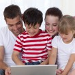 Royalty-Free Stock Photo: Family at home using a laptop