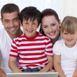 Smiling family at home using a laptop — Stock Photo