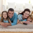 Smiling family on floor in living-room — Stock Photo #10298760