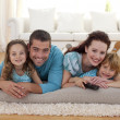 Stock Photo: Smiling family on floor in living-room