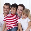 Royalty-Free Stock Photo: Happy family sitting on sofa together