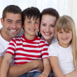 Portrait of happy family sitting on sofa together — Stock Photo #10298765