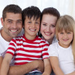 Stock Photo: Portrait of smiling family sitting on softogether