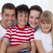 Portrait of smiling family sitting on sofa together — Stock Photo