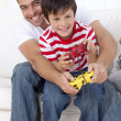 Smiling father and kid playing video games at home - Stock Photo