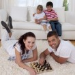 Couple playing chess on floor in living-room — Stock Photo #10298792