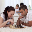 Parents playing chess on floor in living-room — Stock Photo #10298794