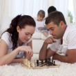 Parents playing chess on floor in living-room — Stock Photo
