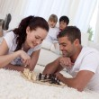 Smiling couple playing chess on floor in living-room — Stock Photo #10298795