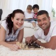 Happy couple playing chess on floor in living-room — Stock Photo #10298796
