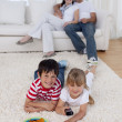 Happy children watching television on floor in living-room — Stock Photo