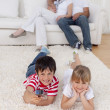 Brother and sister watching television on floor in living-room — Stock Photo #10298804