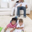 Brother and sister painting on floor in living-room — Stock Photo