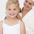 Smiling mother doing daughter's hair — Stock Photo #10298828