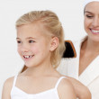 Young mother doing daughter's hair — Stock Photo #10298832