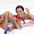 Couple playing videogames in bed — Stock Photo