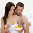 Young couple eating fruit in bed — Stock Photo #10298906