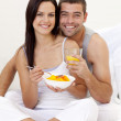 Couple eating fruit and orange juice in bed — Stock Photo