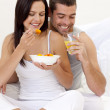 Couple having nutritive breakfast in bed — Stock Photo