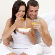 Woman and man having nutritive breakfast in bed — Stock Photo