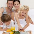Stock Photo: Family eating breakfast in bedroom