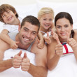 Family playing in bed with thumbs up — Stock Photo #10298970