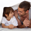 Father and son talking under the bedsheets — Stock Photo