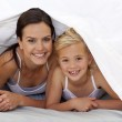 Mother and daughter under the bedsheets — Stock Photo