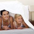 Mother and daughter under the sheets — Stock Photo