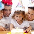 Little girl celebrating her birthday with her parents — Stock Photo