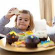 Happy little girl eating confectionery at home — Stock Photo