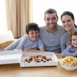 Family eating pizza and fries at home - Stock Photo