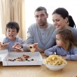 Stock Photo: Family eating pizza and fries at home