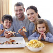 Stock Photo: Parents and children eating pizzand fries at home